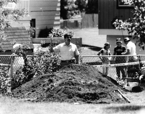 July 7, 1983: A Schaumburg police officer takes a break from digging in the yard of a home on the 600 block of Bahama Lane. Police received a tip that infants had been buried there years before, but officers found no evidence there was any truth to the tip.