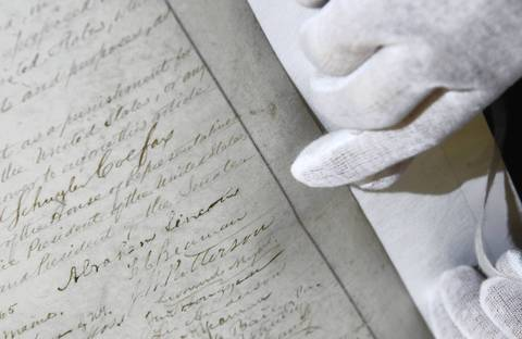 A conservator points to the signature of Abraham Lincoln in a rare copy of the 13th Amendment to the U.S Constitution. The document was being preserved in Chicago for the Lincoln museum in Springfield.
