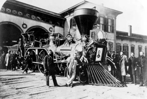 "The locomotive ""Nashville"" of the Cleveland, Columbus and Cincinnati Railroad, leads President Abraham Lincoln's funeral train. The engine was bedecked with bunting, special black-fringed presidential flags and a portrait of the fallen president for part of the trip from Washington to Springfield. The train made stops in 11 cities and helped cement Lincoln's place in Americans' hearts."
