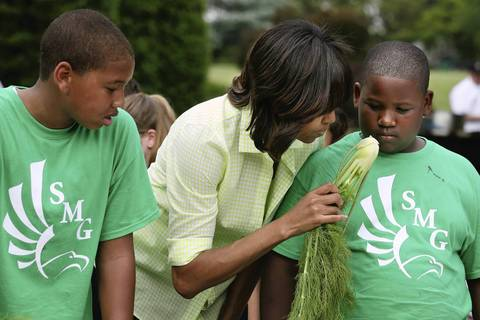 Michelle Obama offers a sniff of fennel to students from Sarah Moore Greene Magnet Technology Academy in Knox County, Tenn., while harvesting and cooking vegetables from the White House Kitchen Garden on May 28, 2013.
