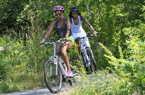 Sasha Obama and first lady Michelle Obama ride bikes Aug. 16, 2013, during a vacation on Martha's Vineyard in West Tisbury, Mass.