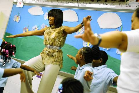 Michelle Obama balances on one leg as she exercises May 24, 2013, with pre-kindergarten children at the Savoy School, one of eight schools selected in 2012 for The Turnaround Arts Initiative at the President's Committee on the Arts and the Humanities, in the Anacostia neighborhood of Washington, D.C.