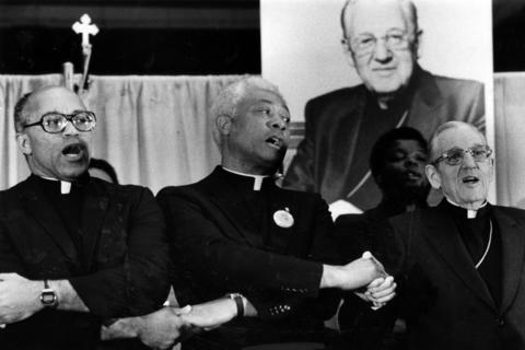"Cardinal John Cody, right, sings ""We Shall Overcome"" on Sept. 20, 1981, with the Rev. George Clements, left, and the Rev. Dominic Carmon during a rally supporting Cody and sponsored by the Black Catholic Clergy of Chicago at the International Amphitheatre."