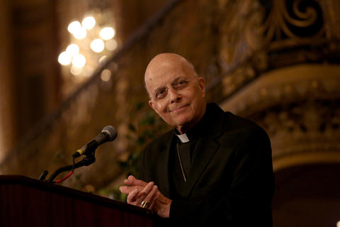 Cardinal Francis George, using a wheelchair and crutches, speaks at Catholic Charities' 97th annual meeting in Chicago on Oct. 2, 2014.