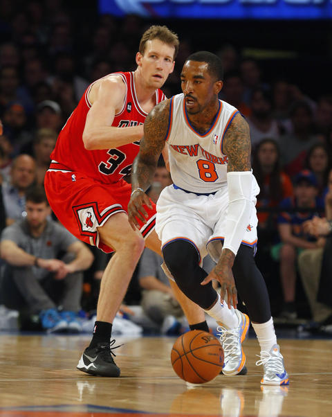 The Knicks' J.R. Smith works against Mike Dunleavy during the first half.