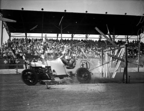 Champion woman race car driver Elfrieda Mais, 41, crashes through a wooden fence during a stunt at the County Fair, circa Aug. 16, 1933. Mais was famous for setting track records and entertaining crowds with daredevil stunts like driving at high speeds through a blazing wooden board wall. Mais was killed on Sept. 27, 1934 when her automobile crashed into a road grader and flipped down an embankment after she had driven it through a blazing board wall at the Alabama State Fair.