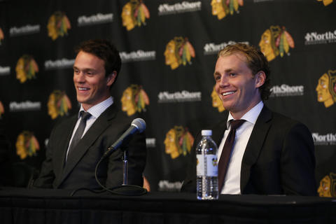 Jonathan Toews and Patrick Kane laugh during a press conference announcing their new contracts.