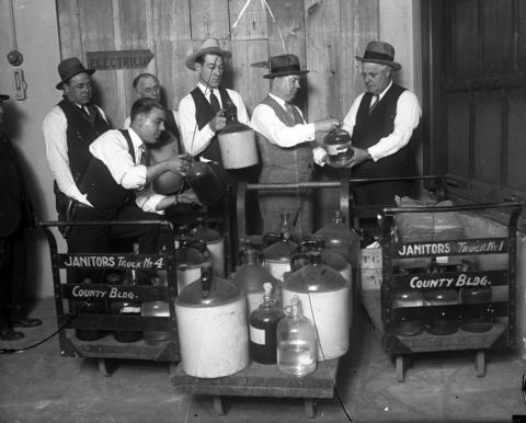 Liquor valued at $50,000 in bootleg prices was poured into the sewer by R. L. Miller, from left, Deputy Sheriff Frank Carsella, George Webster, Deputy Sheriff E. J. Heil, Chief of highway police James Devereaux, and Sheriff Charles E. Graydon on Dec. 29, 1927. The group destroyed 3,000 gallons of alcohol, 1,000 gallons of whiskey, 500 gallons of gin, 750 gallons of wine, and 1,000 pint bottles of ale. Editors note: this glass plate negative is broken in three pieces.