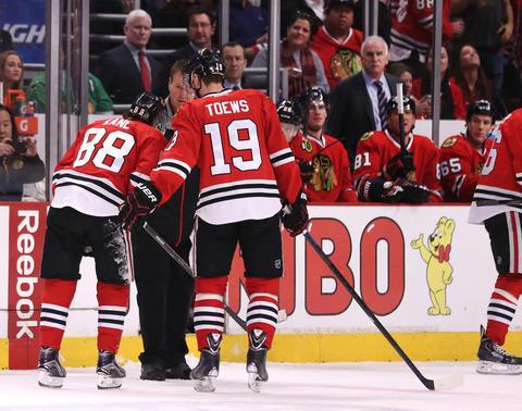 Jonathan Toews skates beside his injured teammate Patrick Kane as Kane heads to the locker room.