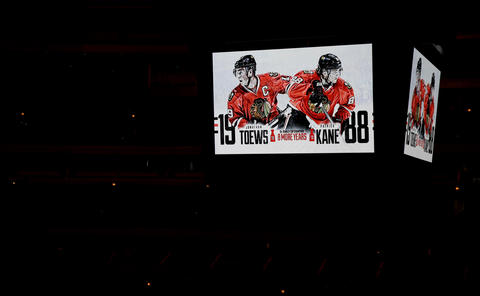 The United Center scoreboard shows images of Jonathan Toews and Patrick Kane as the two players discuss their new contracts at a press conference.