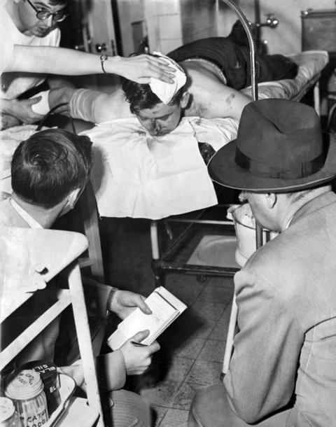 Police question James Earl Ray, 24, of 853 Fullerton Avenue, while he receives first aid at Henrotin Hospital after he dived through a basement window trying to elude police and was then shot by a police cruiser on May 6, 1952. Ray would go on to assassinate Martin Luther King Jr. in 1968.