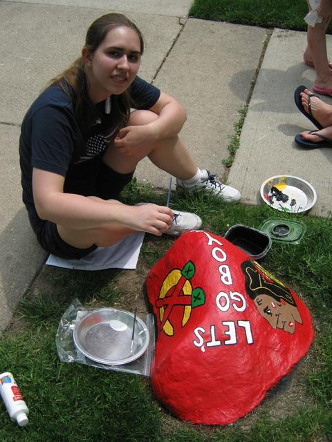 Maddie Gould, a Winnetka resident, paints a neighborhood rock to cheer on the Blackhawks in their quest for the cup.