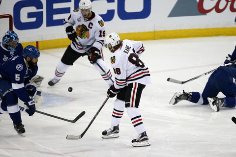 Patrick Kane passes the puck to Jonathan Toews in front of the Lightning goal during the first period in Game 1 of the Stanley Cup Final.