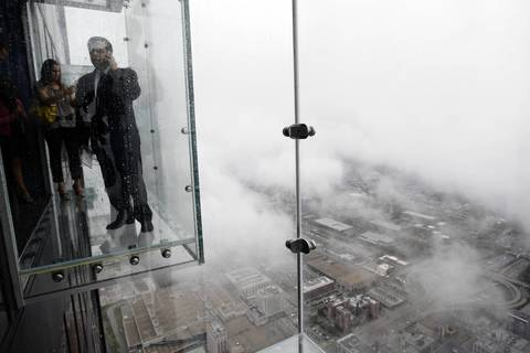 """Journalists check out """"The Ledge,"""" a new addition to the Sears Tower, in July 2009. The enclosed glass ledge juts out from the 103rd floor of Sears Tower, which at the time was the tallest building in the United States."""