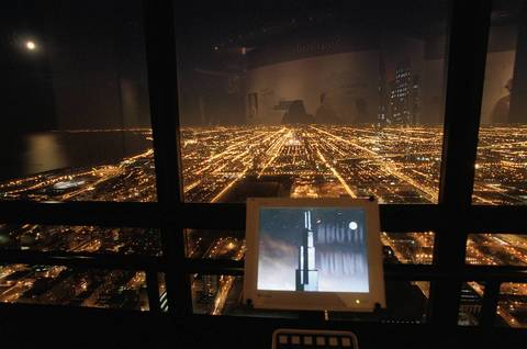 High atop the Sears Tower in the Skydeck, a computer monitor displays a photo of the building as the city lights spread out to the south in 2002. On the monitor the moon shines over the Sears Tower while in live time it rises off to the east.