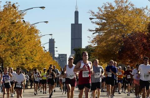 The Sears Towers looms in the background as marathoners run west on Adams Street in Chicago in 2003.