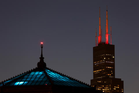 The Shedd Aquarium frames Chicago's Willis Tower, whose antennas are lit in red in support of the Chicago Blackhawks, set to play Game 1 of the Stanley Cup Final on June 3, 2015.