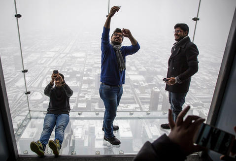 Adil Khan, Zubair Iftekhar and Aamer Khan take photos Feb. 4, 2015, on the Ledge at Willis Tower. The Khans were visiting from India and Iftekhar is a student at UIC.