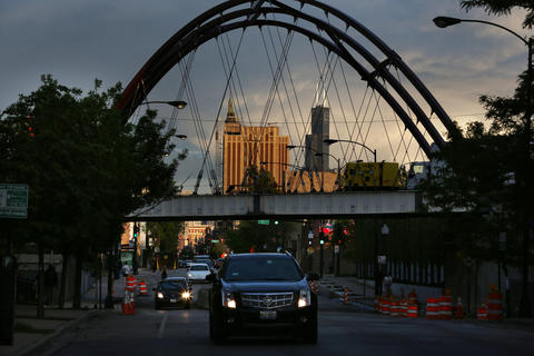 Willis Tower is visible through the most iconic element of the new 606 trail -- a rebuilt bridge over Milwaukee Avenue, painted dark red like the historic bridges over the Chicago River.