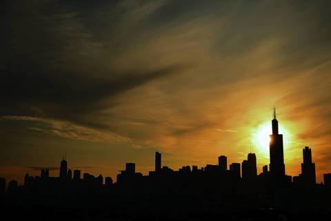 The sun rises behind Willis Tower and the city of Chicago on August 15, 2013.
