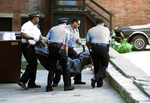 Chicago police officers remove the body of man from the Sutherland Hotel, 4659 S. Drexel Blvd., on July 18, 1995. Officials said the death was linked to the extreme heat.