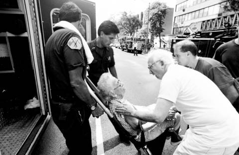 A 101-year-old woman gets help after being overcome by the heat Aug. 13, 1995, after an electrical fire knocked out power in her apartment building.