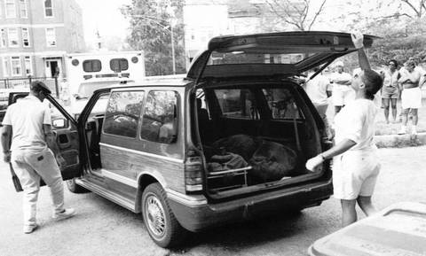 Funeral home employees load a woman's body into a minivan after she died of heat-related causes at a Chicago Housing Authority high-rise on July 18, 1995.
