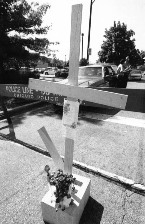 A cross and flowers for those who died during the Chicago area heat wave near the Cook County medical examiner's office July 21, 1995.