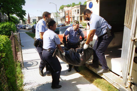 Chicago police officers, including Charley Henson, second from right, carry the body of Marie Brown, who died of heat-related causes from her apartment on July 17, 1995.