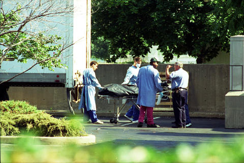 Workers at the Cook County medical examiner's office move a body from one of seven refrigerated trucks, used to store victims of the heat wave, to be processed inside the facility at Harrison and Leavitt streets on July 17, 1995.