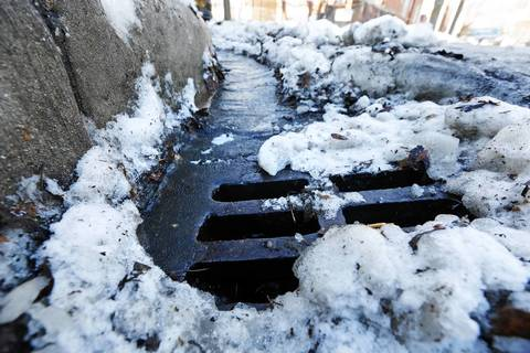 Snow slowly melts into a drain in February 2014 at West Argyle Street and North Lawndale Avenue in the Albany Park neighborhood on a rare day of above-freezing temperatures.