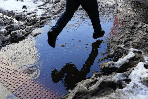 A pedestrian jumps a puddle at Dearborn and Van Buren streets in Chicago as melting snow leaves its mess behind in the Loop in February 2014.