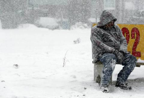 A snow-covered man waits for his bus at California Avenue and Lake Street in February 2014 in Chicago.