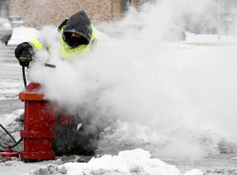 Cicero water department worker Steve Lowe uses blasts of steam to thaw a frozen fire hydrant Jan. 22, 2014, at Cermak Road and Laramie Avenue in Cicero. Firefighters battling multiple major overnight blazes were hampered by frozen hydrants.