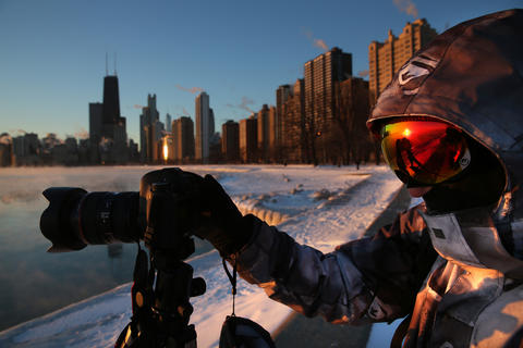 Darek Markiewicz, from Wheeling, is dressed in deep-freeze gear as he photographs the steaming lakefront at North Avenue Beach in Chicago on the morning of Jan. 28, 2014.