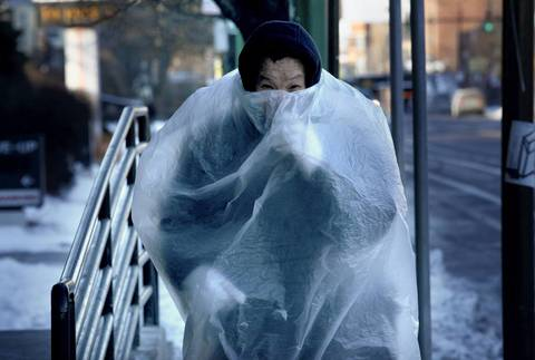 Pak Yu, who lives in Chicago's Chinatown neighborhood, wears a plastic bag over his clothes in January 2014 while walking outside. He said it keeps him warmer.