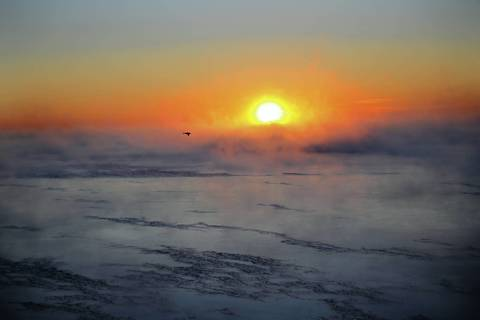 The sun climbs over a steaming horizon along the frozen tundralike Chicago lakefront near North Avenue Beach in late January 2014.