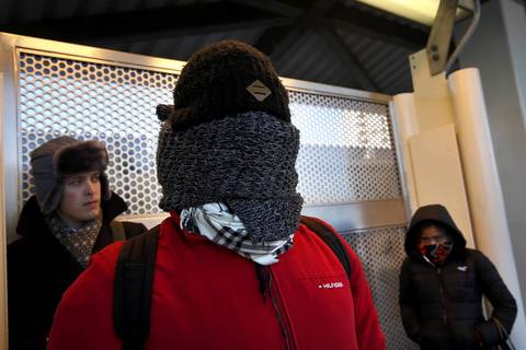 "Jonathan Allen takes full cover Jan. 27, 2014, as he waits at the Howard Avenue ""L"" station in Chicago for a train to his job at the Jewish Community Center in Skokie."