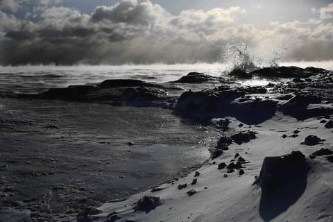 Steam rises from Lake Michigan, at Howard Avenue in Chicago, as waves break over the shoreline, creating a lunarlike landscape Jan. 27, 2014.