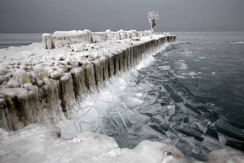 The pier at 39th Street is coated with ice and bordered by broken ice that looks like shards of glass.