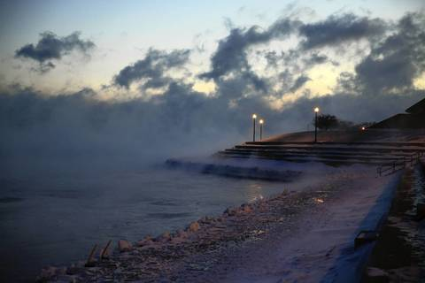 Fog and snow blow across Lake Michigan as the sun rises near the Adler Planetarium in Chicago on Jan. 6, 2014.