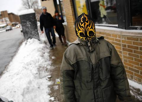 Christopher Escoto, 7, wears his wrestling mask to guard against the cold Jan. 3, 2014, while walking with his parents Jose Bran, background, and Maris Bautista on North Central Avenue in Chicago.