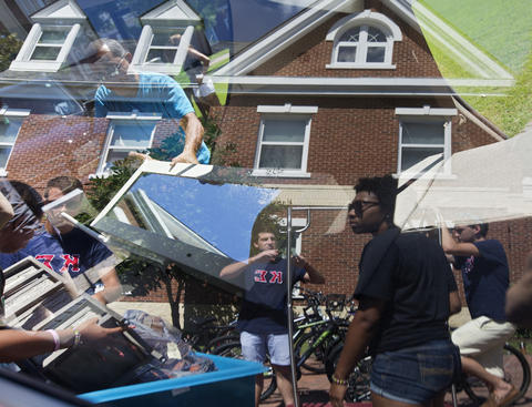 Christopher Newport University students help unload belongings from a vehicle as freshmen move in to York River West dorm on Saturday.