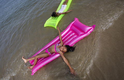Denym Batten, 7, and Leaylum Parker Jones, 7, play on inflatable rafts at Buckroe Beach as temperatures hovered in the 90s on Monday afternoon.
