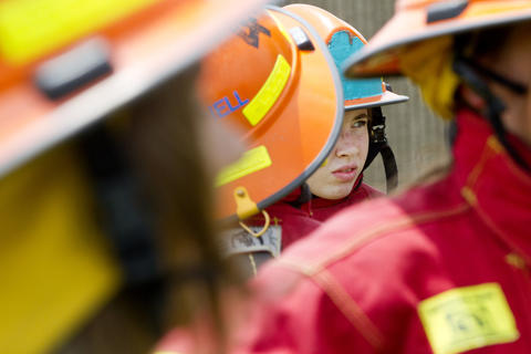 Young girls wait for instructions after getting into full firefighting gear on their first day at Camp Fury, a camp for girls hosted by the Hampton Division of Fire and Rescue.