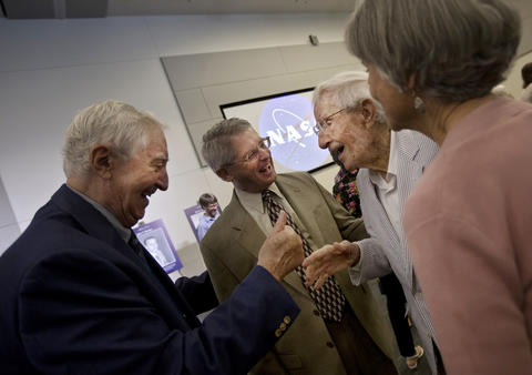 Duncan McIver, left, congratulates Langley Research Center NACA and NASA Hall of Honor inductee John Becker, 101, second from right, following the conclusion of a ceremony on Thursday at NASA Langley.