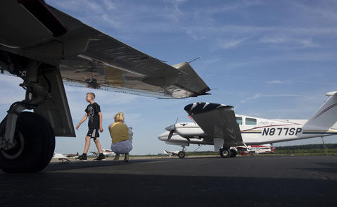 Michael Hagerman walks by Michelle Walters as they wait to fly with Hampton Roads Air Tours from the Norfolk Flight Center on Tuesday in Chesapeake.