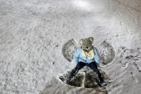 Christopher Newport University student Amy Saunders sits up after making a snow angel on the campus Monday evening.