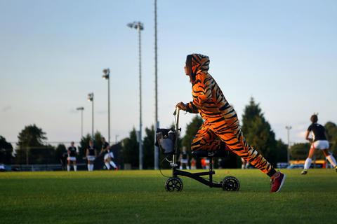 Kaila Atkins, 17, rides a scooter across the grass before the start of Wednesday's field hockey game against Smithfield. Atkins, a senior on the team, broke her foot three weeks ago and came dressed in a tiger suit to support her teammates.
