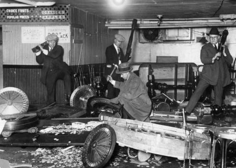 Capt. John Sage and his men smash thousands of dollars worth of gambling apparatuses after raiding a gambling house just hours before in 1926.